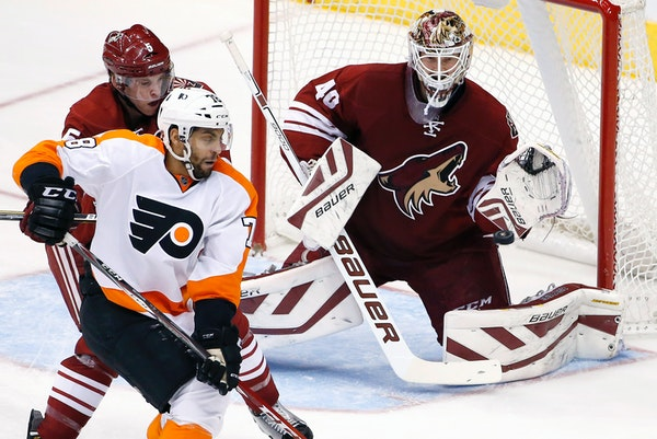 Arizona Coyotes' Devan Dubnyk (40) makes a glove save on a shot as Coyotes' Connor Murphy (5) defends against Philadelphia Flyers' Pierre-Edouard Bell