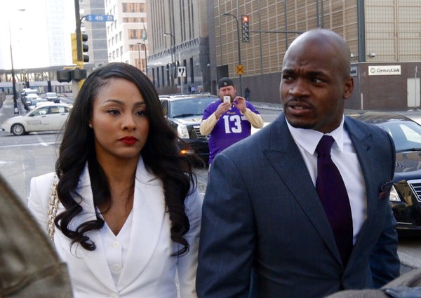 Adrian Peterson and his wife, Ashley, walk to U.S. District Court in downtown Minneapolis on Friday, Feb. 6, 2015. The hearing is the first step in a