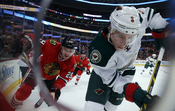 Blackhawks left wing (and Wild killer) Bryan Bickell (29) and Wild center Charlie Coyle battled along the boards during the first period. Bickell late