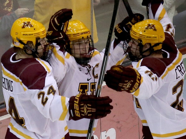 Gophers Hudson Fasting, left and Connor Reilly celebrated with Kyle Rau after scoring the overtime goal at the end of the game.