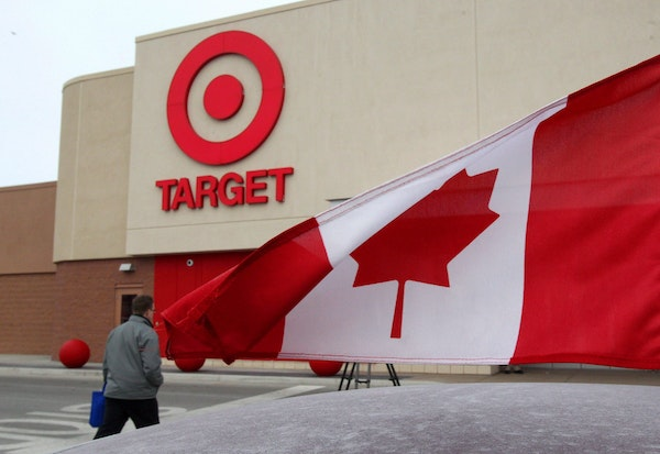 In this March 5, 2013 photo, a Canadian flag flies on the car of a customer's car parked in front of a Target store in Guelph, Ontario.