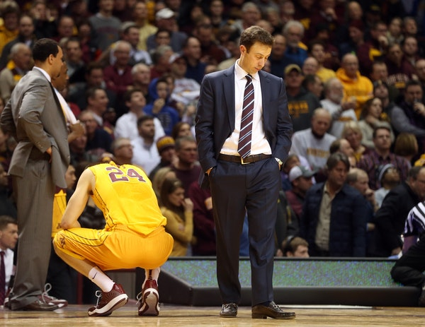 Minnesota head coach Richard Pitino looks at the floor as officials, right, review a last second basket which would have tied an NCAA college basketba