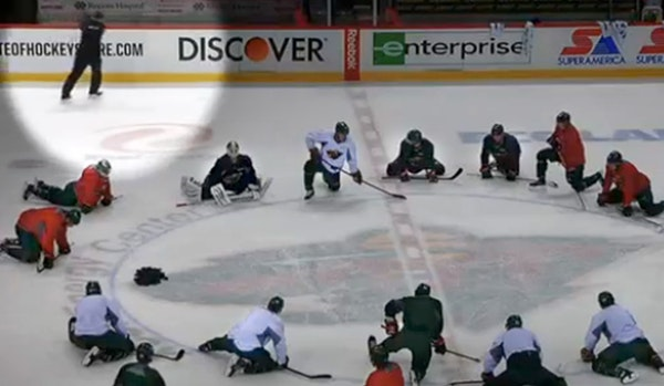 After peppering his team with expletives and sending it to center ice to stretch, Wild coach Mike Yeo (spotlighted) slammed his stick against the visi