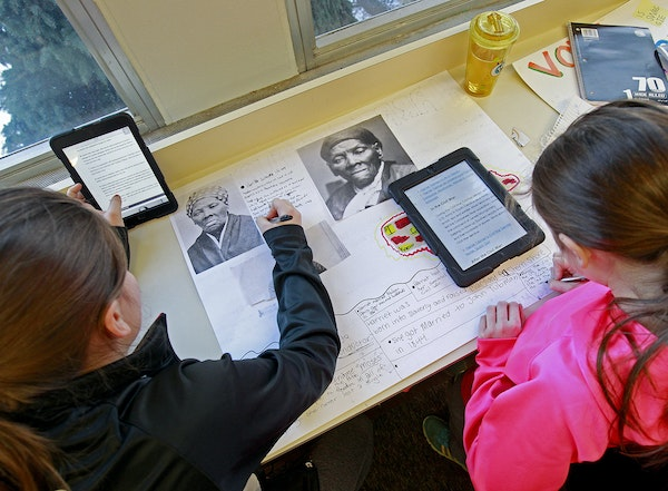 """Elli Andriano-Allard, 10, left, and Megan Liebers, 10, worked on their """"hero project"""" at Gateway Academy in Farmington."""