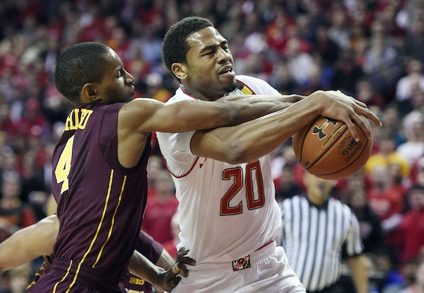 Maryland guard Richaud Pack, right, drives to the basket as Minnesota guard Deandre Mathieu defends during the first half of an NCAA college basketbal