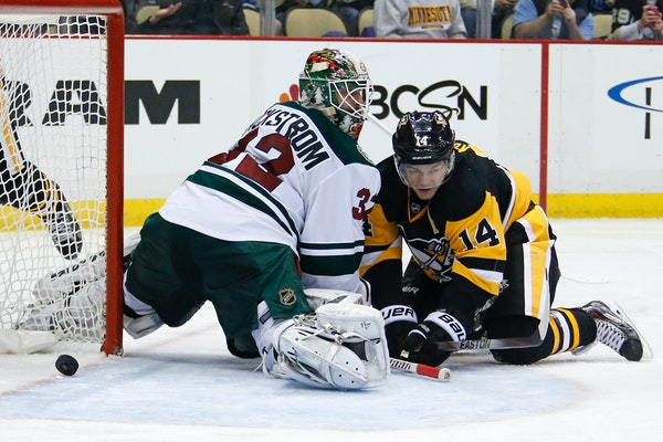 Pittsburgh Penguins' Chris Kunitz (14) gets a shot behind Minnesota Wild goalie Niklas Backstrom (32) for a goal in the second period of an NHL hockey