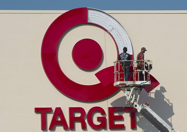 In this July 20, 2013 photo, workers install an outdoor sign at the new Target store at the Mic Mac Mall in Dartmouth, Nova Scotia. On Thursday, Jan.