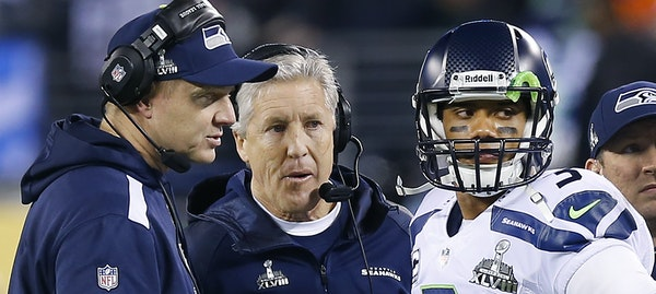 The Seahawks' Darrell Bevell (left, with head coach Pete Carroll and quarterback Russell Wilson) manages Wilson differently than he did risk-taking