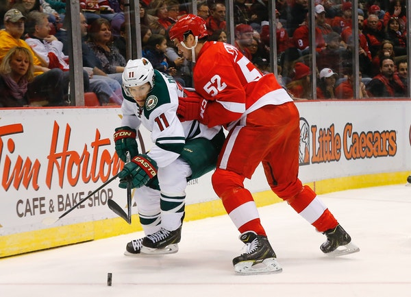 Detroit Red Wings defenseman Jonathan Ericsson (52) defends Minnesota Wild left wing Zach Parise (11) in the first period of an NHL hockey game in Det