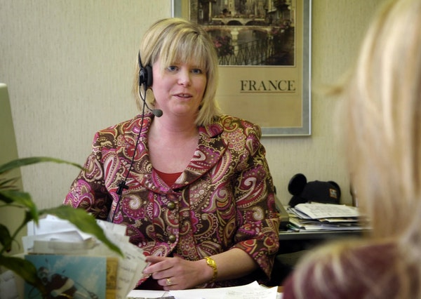 A travel agent assists a client with travel plans.