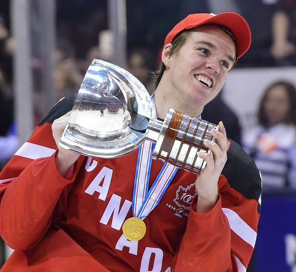 Canada's Connor McDavid skates with the trophy following his team's 5-4 win over Russia in the title game at the hockey World Junior Championship in T