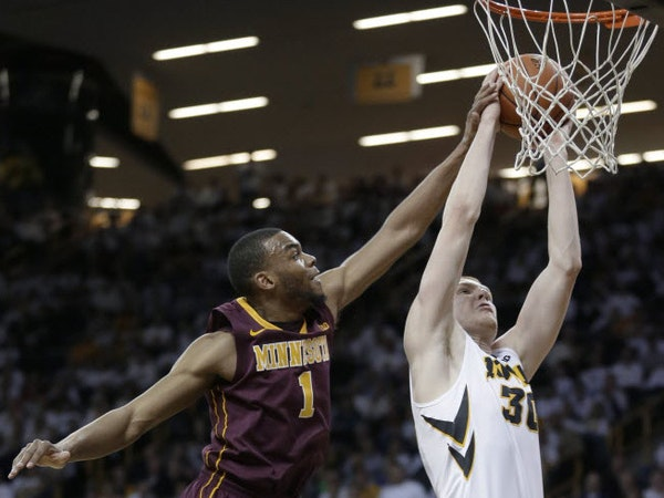 Iowa forward Aaron White, right, drives to the basket past Minnesota guard Andre Hollins during the first half Thursday in Iowa City.