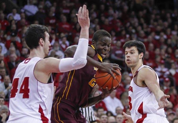 Minnesota's Bakary Konate, center, battles between Wisconsin's Frank Kaminsky (44) and Duje Dukan during the first half of an NCAA college basketball