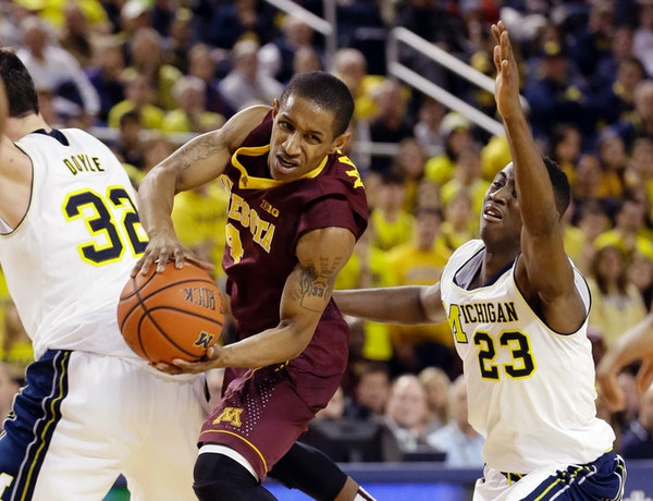 Minnesota guard DeAndre Mathieu looks to pass between Michigan forward Ricky Doyle (32) and guard Caris LeVert (23) during the first half of an NCAA b