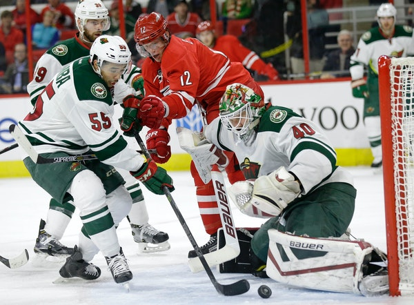 Carolina Hurricanes' Eric Staal (12) tries to shoot against Minnesota Wild's Matt Dumba (55) and goalie Devan Dubnyk (40) during the second period of