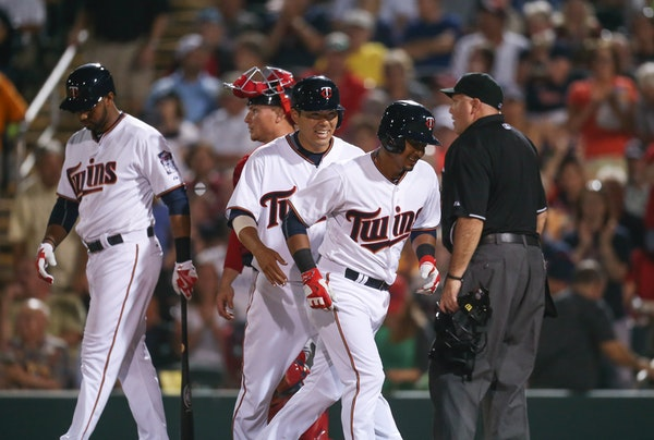 Minnesota Twins Eduardo Escobar, foreground, and Kurt Suzuki headed for the dugout after Escobar hit a two run homer in the third inning that scored S