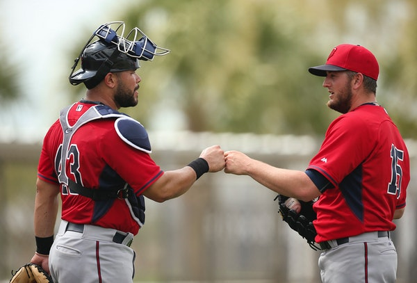 Twins catcher Josmil Pinto and pitcher Glen Perkins bumped fists after Pinto caught for Perkins during batting practice at Hammond Stadium.