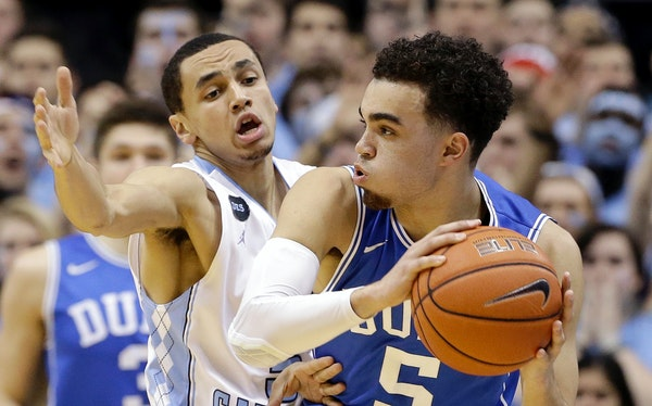 North Carolina's Marcus Paige, left, guards Duke's Tyus Jones (5) during the first half of an NCAA college basketball game Saturday, March 7, 2015 in