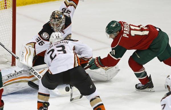 Anaheim Ducks' Francois Beauchemin, left, helps goalie John Gibson defend the net as Minnesota Wild's Zach Parise, right, attempts a shot in the f