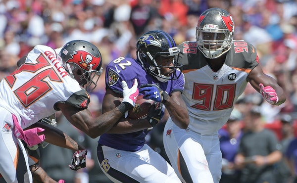 Baltimore Ravens wide receiver Torrey Smith (82) tries to gain yardage after a reception between Tampa Bay Buccaneers cornerback Crezdon Butler (26) a