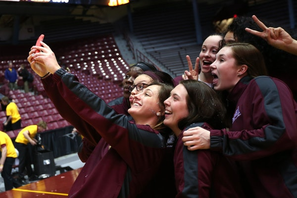 Shayne Mullaney, with Rachel Banham to her right, took a group selfie after the Gophers' NCAA bid became a reality on Monday.