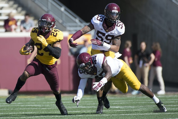 University of Minnesota running back Rodney Smith (24) breaks past defenders Adekunle Ayinde (45) and Ray Dixon (59) during the first half of Saturday