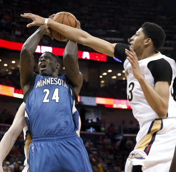 Pelicans forward Anthony Davis (23) fouled Wolves forward Anthony Bennett (24) during the first half Sunday in New Orleans.