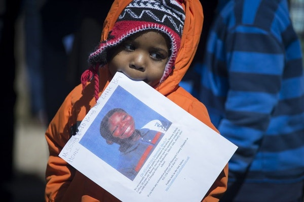 A young boy takes part in a community gathering marking the tenth day since the disappearance of 10-year-old Barway Collins, in Crystal, Minn. on Satu