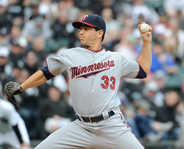 Minnesota Twins starting pitcher Tommy Milone (33) throws against the Chicago White Sox during the first inning of a baseball game, Friday, April 10,