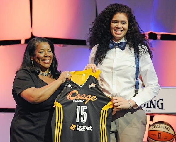 Minnesota's Amanda Zahui B., right, holds up a Tulsa Shock jersey with WNBA president Laurel J. Richie after the Shock selected Zahui B. as the No. 2