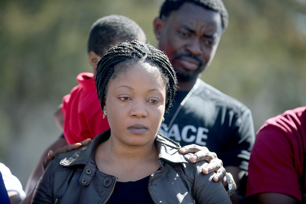 Yamah Collins is comforted by her family members as Pastor Harding Smith made a statement regarding formal charges against her husband Pierre Collins,