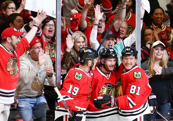 Jonathan Toews (19), Brandon Saad (20) and Marian Hossa (81) celebrated a goal by Saad in the first period of Game 1 against the Wild.