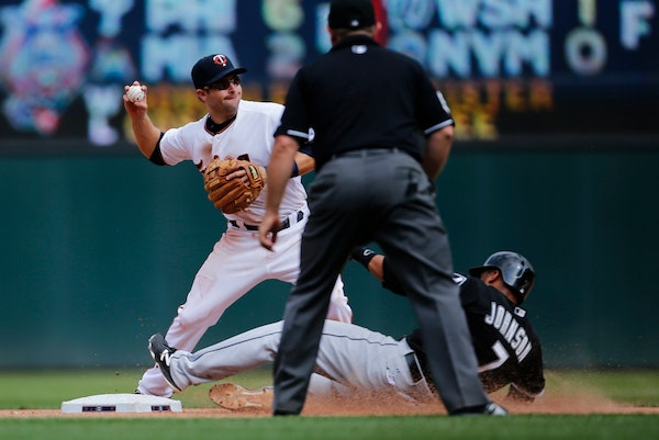 Twins second baseman Brian Dozier tags out White Sox infielder Micah Johnson before trowing the ball to Kennys Vargas at first for a double in the sev