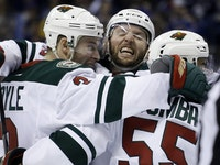 Minnesota Wild's Charlie Coyle, left, is congratulated by teammates Thomas Vanek, of Austria, and Matt Dumba, right, after scoring during the third pe