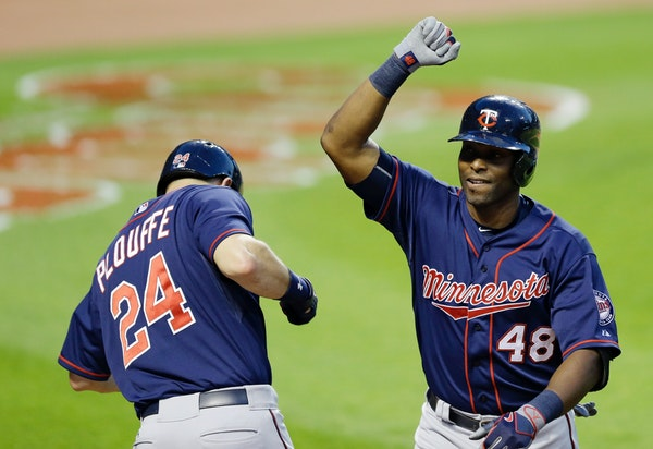 Minnesota Twins' Torii Hunter (48) is congratulated by Trevor Plouffe (24) after Hunter hit a solo home run off Cleveland Indians starting pitcher Tre