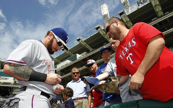 Before his first major league game of 2015, and back with his old team, Texas' Josh Hamilton signed an autograph for a fan on Monday.