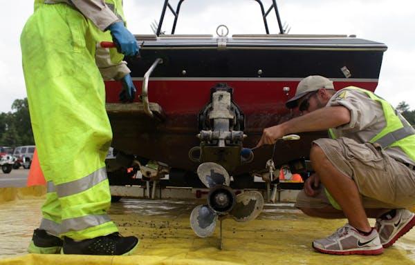 Joe Hale and Ben Troop, DNR Watercraft Inspectors, scrub dead zebra mussels off a boat that had been fined $300 for not following aquatic invasive spe