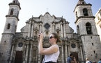 Sarah Grimes, a violinist in the Minnesota Orchestra, takes photos in Plaza de la Catedral in Old Havana, Cuba on Wednesday.