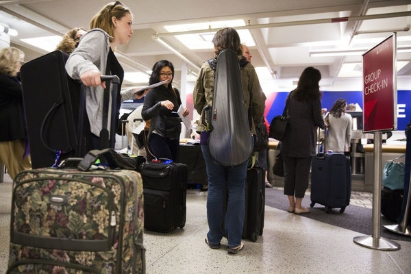 Minnesota Orchestra musicians line up to check in at the Delta counter at Minneapolis - St. Paul International Airport on Wednesday, May 13, 2015.