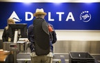 Minnesota Orchestra saxophone player Jim Romain checks in at the Delta counter at Minneapolis - St. Paul International Airport on Wednesday, May 13, 2