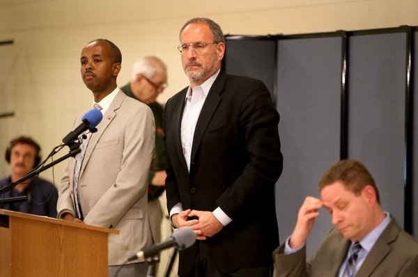 U.S. Attorney Andy Luger, center, and Richard Thornton, the FBI's special agent in charge of the Minneapolis office, right, were with Sadik Warfa, lef