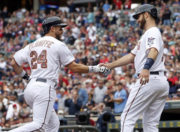Trevor Plouffe, left, is congratulated by Joe Mauer after Plouffe's three-run home run off Boston Red Sox pitcher Joe Kelly in the second inning of a