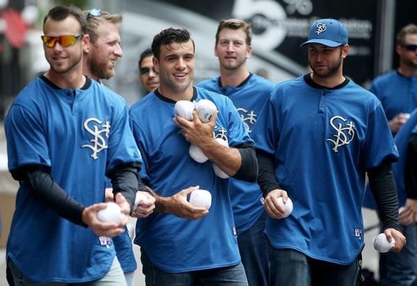 Catcher Vinny DiFazio, center, carried soft baseballs that St. Paul Saints players passed out near new CHS Field on Wednesday.