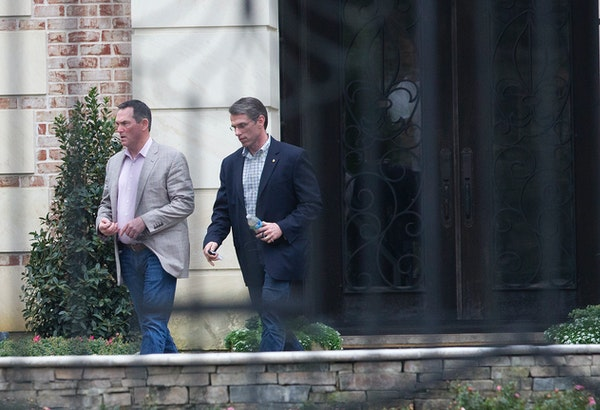 Minnesota Vikings head coach Mike Zimmer, left, and general manager Rick Spielman leave the home of NFL running back Adrian Peterson, Wednesday, March