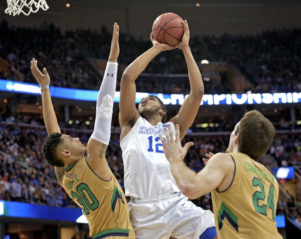 Kentucky's Karl-Anthony Towns (12) shoots against Notre Dame's Zach Auguste (30) and Pat Connaughton during the NCAA tournament.