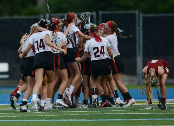 Eden Prairie players celebrated their third state title in girls' lacrosse, while a lone Lakeville South player buried her head.