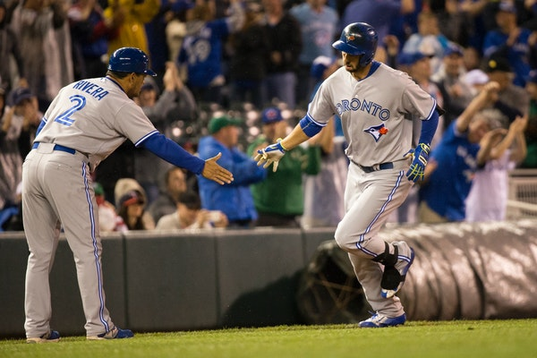 Chris Colabello high fived third base coach Luis Rivera as he rounded the bases after hitting a two-run homer in the top of the ninth against the Twin