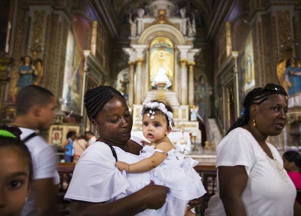 Paula Arozareala holds five-month-old Patricia Alejandra before her baptism in Iglesia de la Merced in Havana, Cuba on Saturday, May 16, 2015. ] LEILA