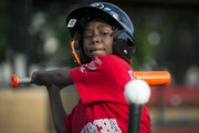 Seven-year-old Ja'Kiya, wearing a Monarchs jersey, prepared to hit the ball during a scrimmage last month.