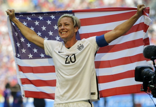 United States' Abby Wambach holds up the U.S. flag as she celebrates after the U.S. beat Japan 5-2 in the FIFA Women's World Cup soccer championship i